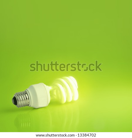 A vibrant presentation of a modern energy-saving lightbulb lit on a lush green background.  Plenty of copyspace, ideal for ecology, energy concepts or imagination and marketing pitches - stock photo