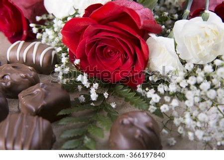 "A vibrant red rose and chocolate candies to say ""I Love You"" - stock photo"