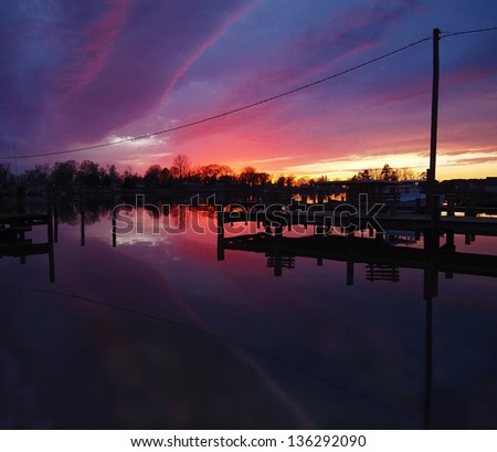 A vibrant sunset is reflected on the water of a quiet cove with docks, trees, and a boat, in the evening.