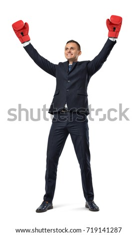 A victorious and smiling businessman keeps his arms up while wearing red boxing gloves. Business and competitors. Corporate rivalry. Winner at everything.