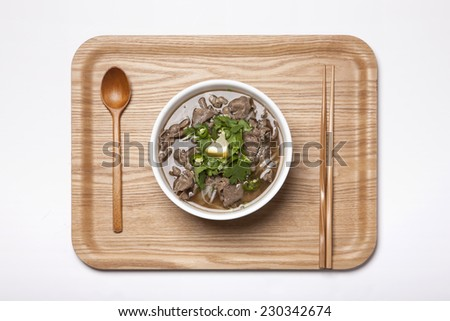 A Vietnam rice noodles with beef and wood spoon, chopsticks, wood tray isolated white, top view at the studio. - stock photo