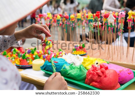 "A Vietnamese crafstwoman is shaping ""to he"" toy, which is made of powder and colorful dyes."