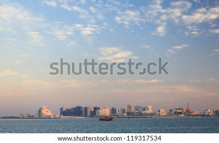 A view across Doha Bay, Qatar, at sunset. The Museum of Islamic Art is to the left of the skyline and the spiral minaret of the Qassim Darwish mosque to the right, with a dhow between. - stock photo