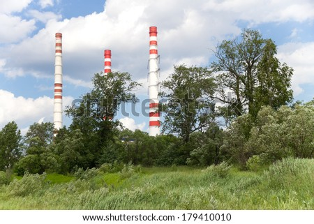 A view across manufacturing pipe on a cloudy day. Forest, sky an - stock photo