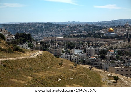 A view at the holy Muslim Dome of the Rock and Al-Aqsa mosque behind the surrounding wall of the old city of Jerusalem. On the left side of the image, part of Mount of the Olives is seen. - stock photo