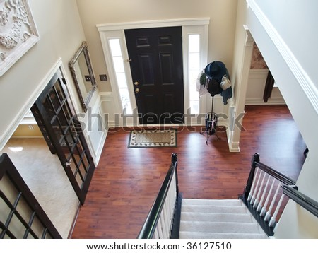 A view down a stairway in a modern american home. Carpeted stairs and a wooden banister and railing are visible, and there is a hatstand in the corner - stock photo