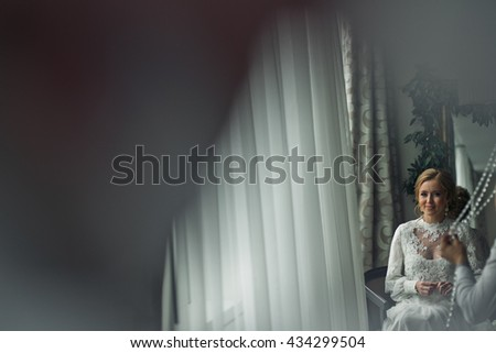 A view from afar on a smiling bride, which sits on the chair in hotel room - stock photo