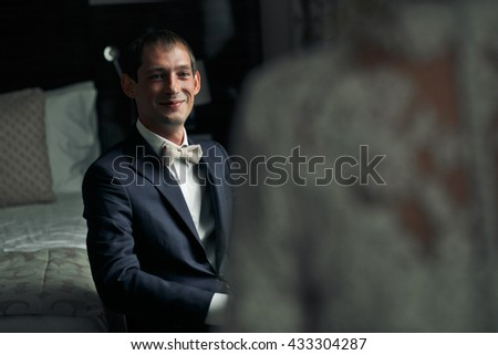 A view from bride's shoulder on a groom who smiles while sitting in the chair