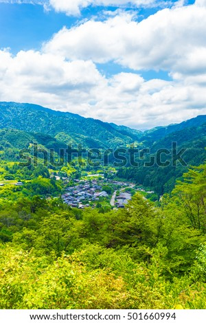 A view from high angle viewpoint and former grounds of Tsumago castle overlooking Tsumago village above the Magome-Tsumago portion of ancient Nakasendo Route in Japan on a blue sky day. Vertical