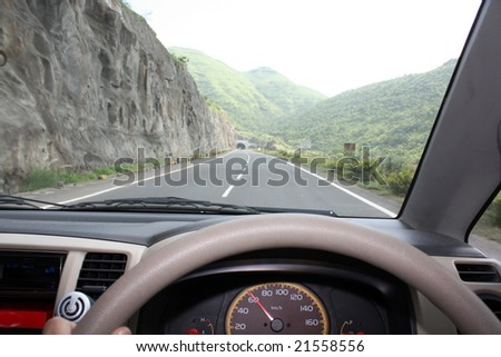A view from the driver's seat, of a car driving at the speed of 60 on an expressway. Focus is on speedometer.