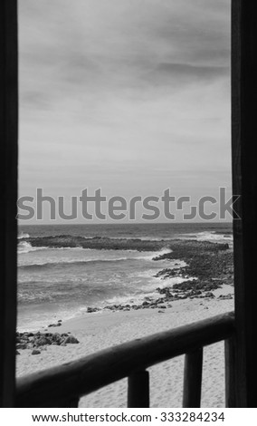 A view from the wooden terrace through the opened window on ocean beach. Algarve, Portugal. Selective focus on the landscape. Aged photo. Black and white. - stock photo