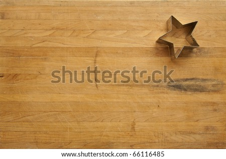 A view looking down on a single metal star cookie cutter on a worn butcher block cutting board - stock photo