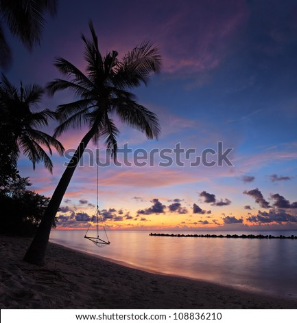 A view of a beach with palm trees and swing at sunset, Kuredu island, Maldives, Lhaviyani atoll