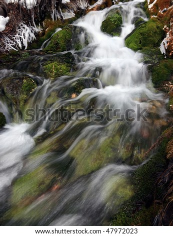 A view of a beautiful spring flowing over mossy rocks