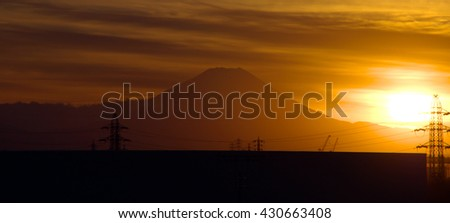 A view of a beautiful sunset illuminating the silhouette of Mount Fuji seen on the horizon, with some cirrus clouds in the orange sky.  Taken in Saitama prefecture, Japan. - stock photo