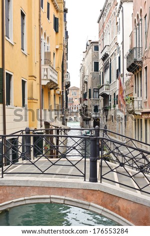 A view of a bridge and a water way between apartment buildings. - stock photo
