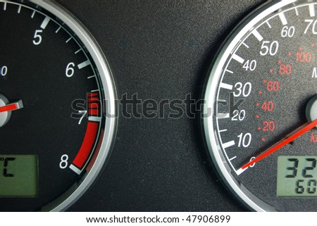A view of a car instrument panel showing speedometer and rev counter