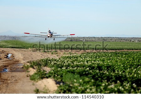A view of a crop duster spraying green farmland. - stock photo