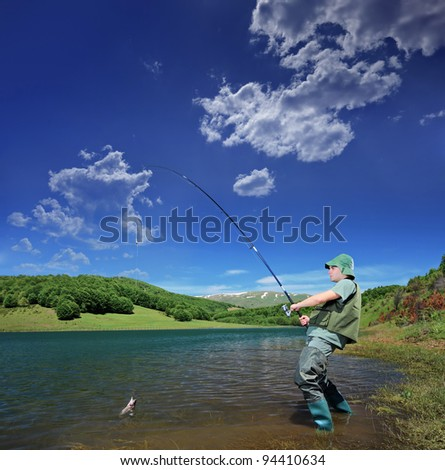 A view of a fisherman fishing on a Mavrovo lake, Macedonia - stock photo