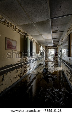 A view of a flooded and reflective hallway inside the abandoned Hudson River State Hospital in New York.
