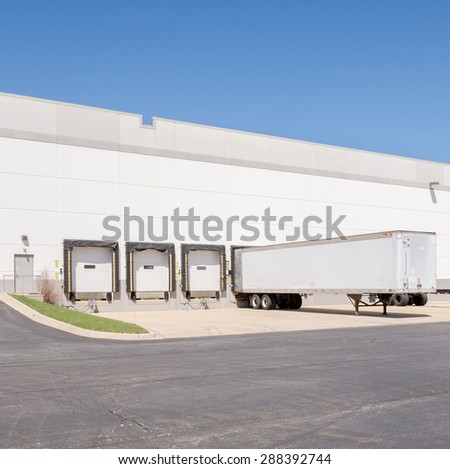 A view of a giant Logistics warehouse with multiple loading docks - stock photo