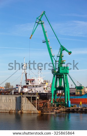 A view of a large ship under repair in dry dock at a shipyard.  - stock photo