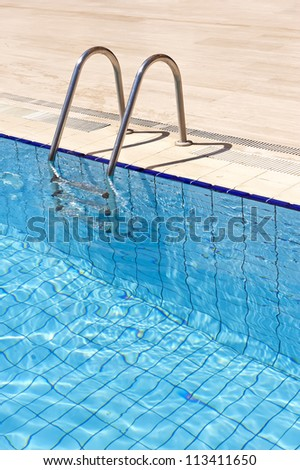 A view of a  light clear blue swimming pool with steel ladder. - stock photo
