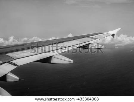 A view of a passenger jet wing as seen from the cabin during flight