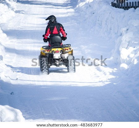 A view of a person riding a four-wheel recreational vehicle (RV) down a snowy road on a cold winter day.