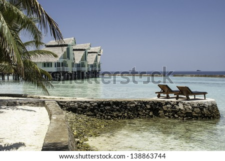 A view of a tropical lagoon with waterhuts and lounge chairs.
