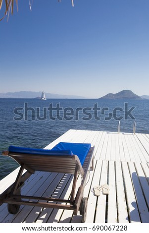A view of a white wooden beach trestle on a wooden pier in the foreground and a sailing yacht in a small sea bay surrounded by mountains