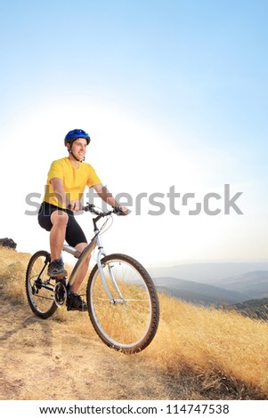 A view of a young biker riding a mountain bike on a sunset, Macedonia - stock photo