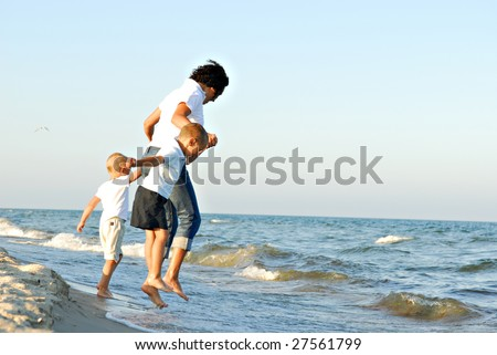 A view of a young woman and two young boys holding hands and jumping on a beach as waves and surf reach the shore.