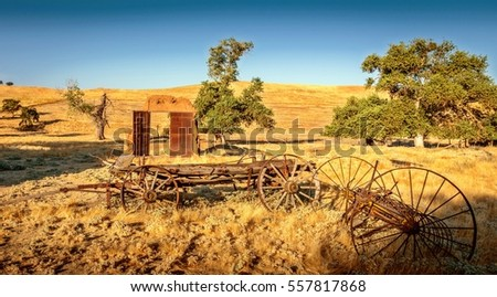 A view of an old machinery in rural farmland California.