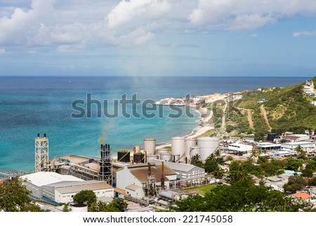 A view of bay on St Martin from hill with sugar factory on coast - stock photo