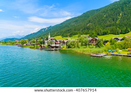 A view of beautiful green water Weissensee alpine lake and village in summer landscape of Alps Mountains, Austria - stock photo