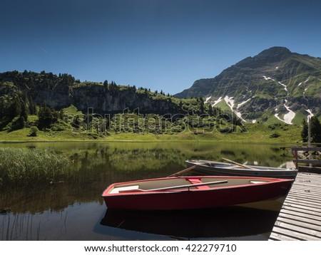 A view of boats that anchor at the bridge of Koerbersee lake around the village Schroecken in Bregenzerwal, region Vorarlberg, Austria - stock photo