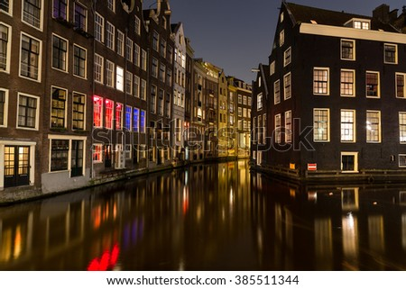 A view of buildings along the canals in Amsterdam in the Centrum Borough and De Wallen Area. Taken at Night. There is space for text. - stock photo