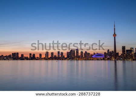 A view of buildings West of Downtown at dusk from Lake Ontario with copy space above or below the buildings
