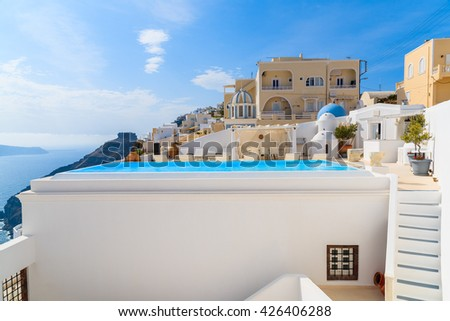 A view of caldera with luxury hotel buildings, typical white architecture of Imerovigli village on Santorini island, Greece - stock photo