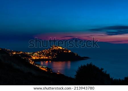 a view of Castelsardo , Sardinia, illuminated by streetlights with the last light of dusk - stock photo