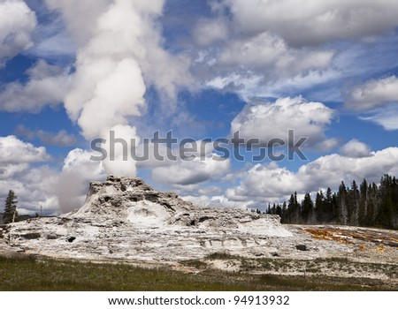 A view of Castle Geyser in Upper Geyser Basin in Yellowstone National Park showing steam rising from the vent in the central cone which has formed over years of steady eruptions. - stock photo