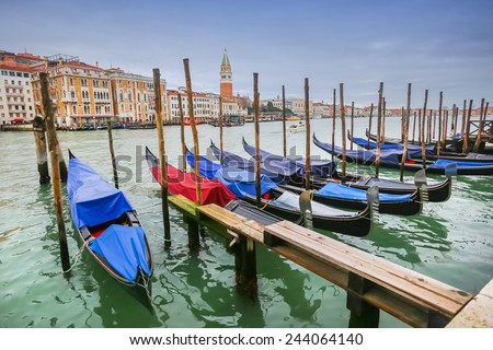 A view of empty gondolas moored and lined up at a gondola dock in a water canal in Venice, Italy. - stock photo