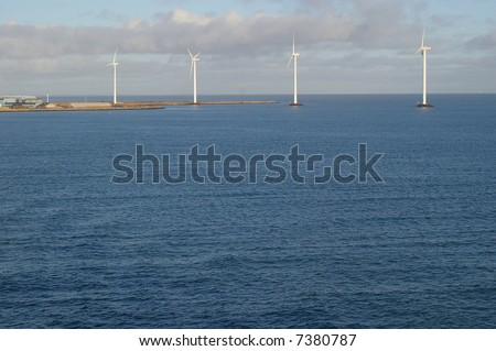 A view of four tall wind-powered electricity generators built just offshore in Frederikshavn, Denmark.