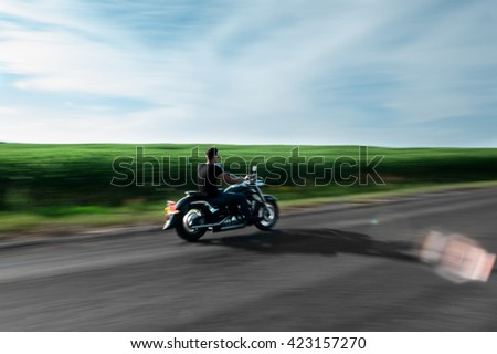 A view of handsome biker riding unknown motorbike with blur movement, speed concept - stock photo