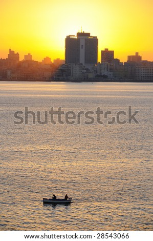 A view of havana skyline at sunset with fishing boat on the front - stock photo
