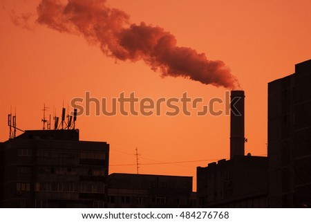 A view of industrial buildings silhouetted against a pinkish sky with steam and smoke streaming from a tall industrial chimney, suggestion city pollution.