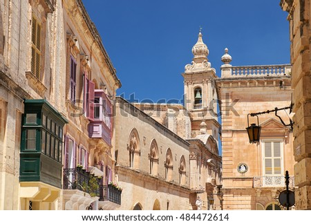 A view of old Mdina street with a residental houses with a traditional Maltese style multicolored balconies and Carmelite Church Bell Tower on the background. Malta.