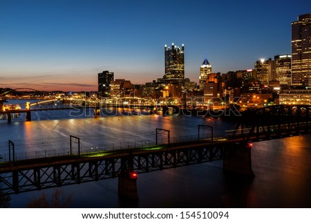 A view of Pittsburgh at dusk taken from Station Square with the T train making light trails across the bridge. - stock photo