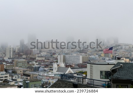 A view of San Francisco on a foggy day from the hill leading to Coit Tower. - stock photo